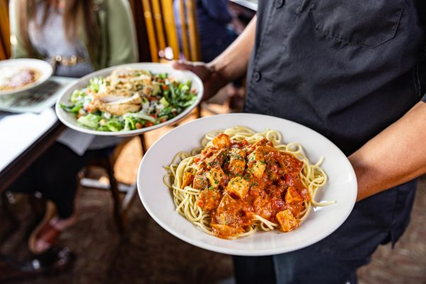 server carrying plate of pasta and plate of salad at The Old Spaghetti Factory