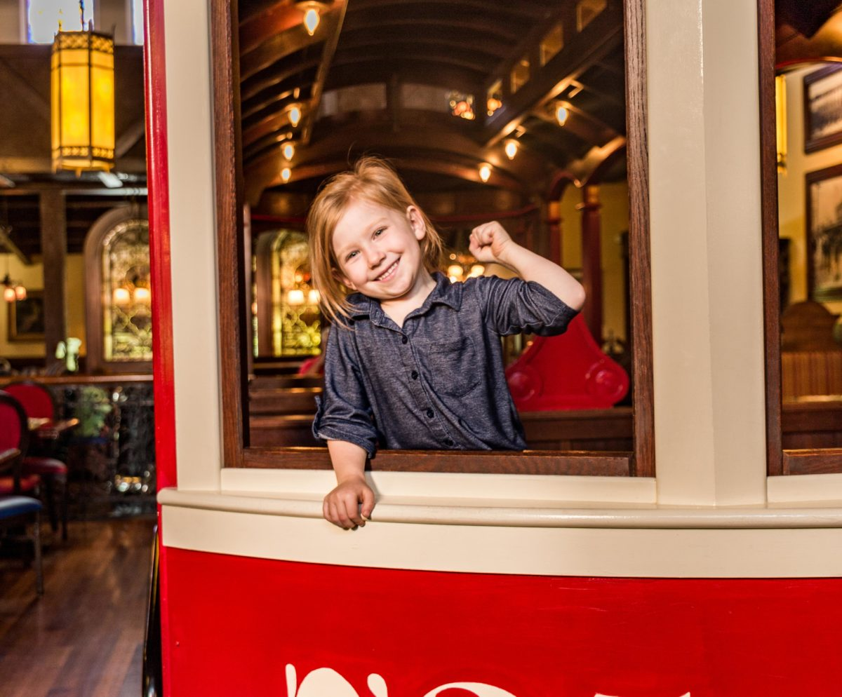 child in trolley smiling at The Old Spaghetti Factory